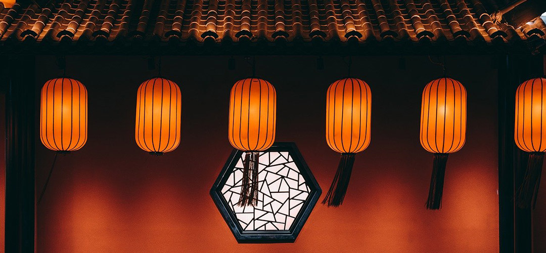 A quiet Chinese temple with a red wall and lanterns hanging outside
